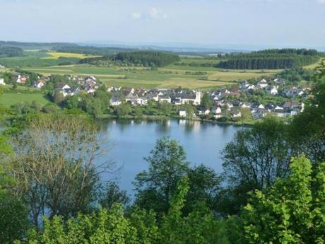 "Near the town of Daun, village houses frame one of the twin crater lakes known as the ""Blue Eyes of the Eifel."""